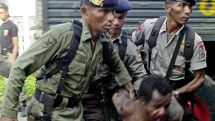 Indonesian anti-riot police arresting a West Papuan pro-separatist.
