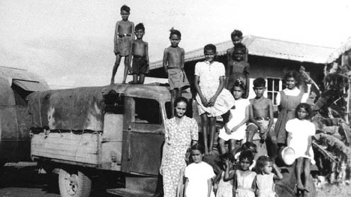 Early undated photo of Lorna Cubillo (far R) seated on truck fender outside the outside the Retta Dixon home in Darwin