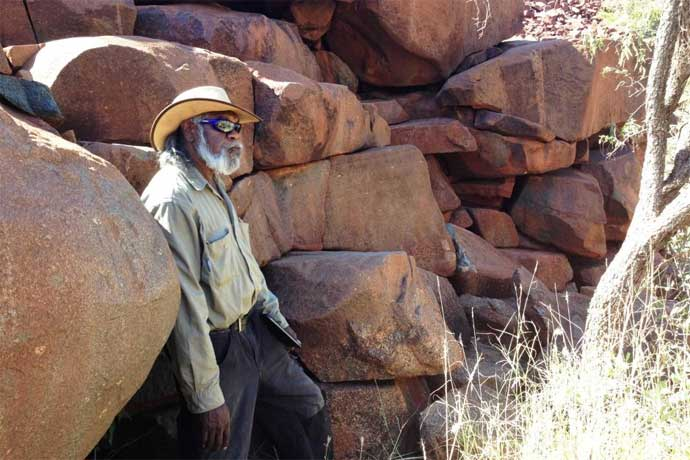 Indigenous ranger Geoffrey Togo stands near the graffiti at Burrup
