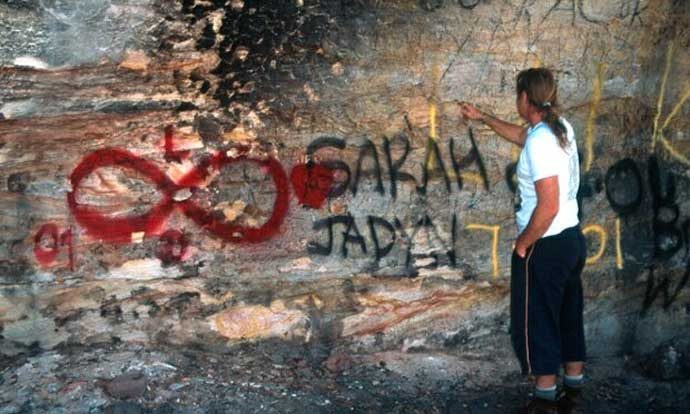 Fire damage and graffiti covering a rock art site