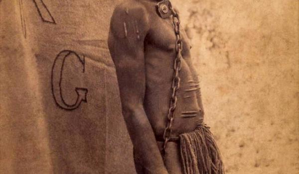 Cumjam, an Aboriginal man accused of murdering Ferguson at Mentana, standing chained by the neck to a tree, Queensland, March 1894 (Pic Alphonse Chargo)is