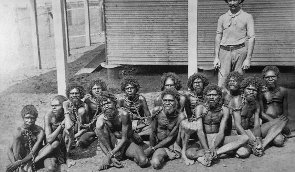 This image shows a boy in chains on the right. This image cropped without the boy may have been by accident or design, but arresting young boys was standard colonial practice. When Royal Commissioner Walter Roth asked why young boys of 14 where being imprisoned he was told by a police officer 'They are able to chuck a spear as well as any older man.'
